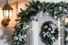 Huisingang voor vakantie wordt verfraaid die De decoratie van Kerstmis slinger van sparrentakken en lichten op het traliewerk Royalty-vrije Stock Foto's