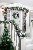 Huisingang voor vakantie wordt verfraaid die De decoratie van Kerstmis slinger van sparrentakken en lichten op het traliewerk Royalty-vrije Stock Foto