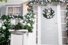 Huisingang voor vakantie wordt verfraaid die De decoratie van Kerstmis slinger van sparrentakken en lichten op het traliewerk Stock Afbeeldingen