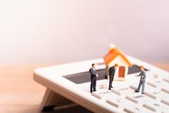 Huismodel en businessmans op calculator met de woordbelasting royalty-vrije stock fotografie