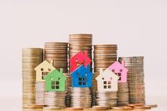 Huismodel op muntstukkenstapel De planning van besparingengeld van muntstukken om een huisconcept, een hypotheek en een onroerend stock fotografie