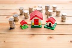 Huismodellen met gestapelde muntstukken Stock Foto's