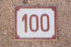 Huisnummer honderd Het rode van letters voorzien op witte achtergrond royalty-vrije stock afbeelding