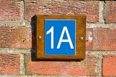 1A huisnummer op muur Stock Afbeeldingen