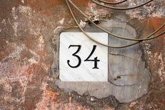 Huisnummer 34 in steen wordt gegraveerd die Royalty-vrije Stock Afbeelding