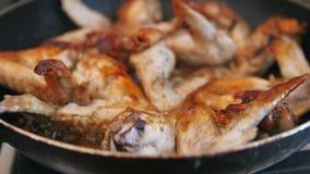Huisongezonde kost - Bradende Kippenvleugels die in kokende olie voorbereidingen treffen stock videobeelden
