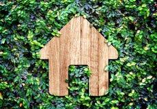 Huispictogram op groene bladerenmuur, Eco-huissysteem Royalty-vrije Stock Afbeeldingen