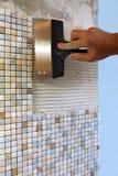 Huisreparatie: het installeren van de mozaïektegel op de muur Stock Fotografie