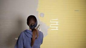 Huisreparatie Het meisje spreidt het pleister op de muur met een grote metaalspatel uit om de pleistervuller op de muur te richte stock video