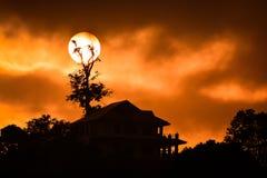 Huissillhouette met volle maan Royalty-vrije Stock Foto's