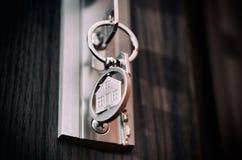 Huissleutel in de deur De zilveren vorm van het tegenhangerhuis Royalty-vrije Stock Afbeeldingen
