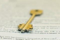 Huissleutel die op een contract van de huurverzekering of hypotheek van de huisverkoop in een onroerende goederenconcept liggen Royalty-vrije Stock Afbeelding
