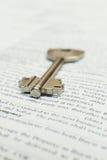 Huissleutel die op een contract van de huurverzekering of hypotheek van de huisverkoop in een onroerende goederenconcept liggen Stock Afbeeldingen