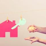 Huissleutel en hand met piggybank Stock Foto's