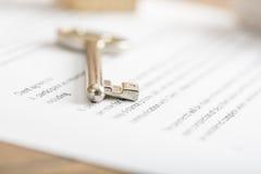 Huissleutel op een contract van huisverkoop Stock Foto