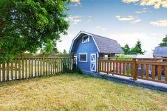 Huistuin op binnenplaats met kleine blauwe schuurloods en houten omheining Royalty-vrije Stock Foto's