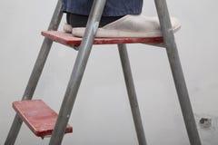 Huisvernieuwing Meester in het uniform op de ladder Stock Afbeeldingen