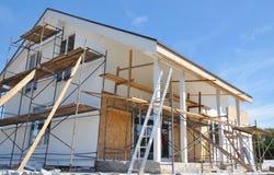 Huisvernieuwing met muurisolatie, het pleisteren, paiting muren Huisbouw met steiger openlucht stock foto