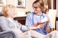Huisverzorger met bejaarde patiënt royalty-vrije stock afbeeldingen