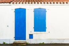 Huisvoorgevel met blauwe zonneblinden en deur Stock Afbeeldingen