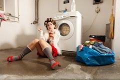 Huisvrouw bored in de wasserij Stock Afbeelding