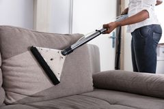 Huisvrouw Cleaning Sofa With Vacuum Cleaner stock afbeelding