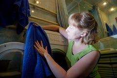 Huisvrouw dichtbij wasmachine in de badruimte en zij is gelukkig met de schone wasserij stock fotografie