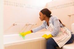 Huisvrouw die badkuip schoonmaken stock afbeelding