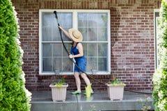 Huisvrouw die de vensters van haar huis wassen stock afbeeldingen