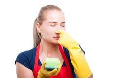 Huisvrouw die haar neus wegens stank stoppen Stock Afbeeldingen