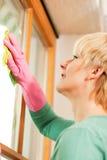 Huisvrouw die haar vensters in rubberhandschoenen schoonmaakt Stock Foto's