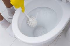 Huisvrouw die het toilet in de badkamers schoonmaken stock afbeeldingen