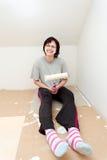 Huisvrouw die na het schilderen van muur aan wit rusten Stock Fotografie