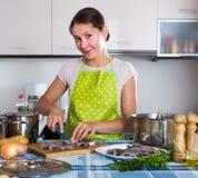 Huisvrouw die nieuw recept van sprattus in keuken proberen Stock Foto