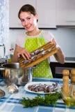 Huisvrouw die nieuw recept van sprattus in keuken proberen Stock Fotografie