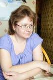 Huisvrouw die op TV in de keuken letten Royalty-vrije Stock Foto