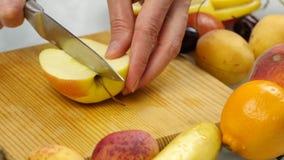 Huisvrouw die thuis de verse vruchten van de salade snijdende appel op scherpe raad voorbereiden vegetarisch gezond voedsel en he stock videobeelden