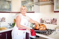 Huisvrouw die versierd geroosterd Turkije op Kerstmis op een keukenachtergrond koken Het concept van dankzeggingsturkije Stock Afbeeldingen