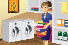 Huisvrouw die wasserij doet Stock Afbeeldingen