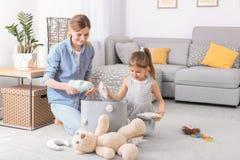 Huisvrouw en dochter die speelgoed opnemen stock afbeeldingen
