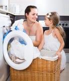 Huisvrouw en haar dochter met linnen dichtbij wasmachine Royalty-vrije Stock Afbeeldingen
