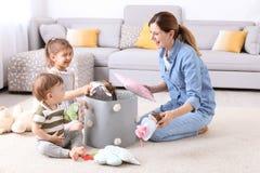 Huisvrouw en kinderen die speelgoed opnemen stock foto's