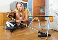 Huisvrouw het schoonmaken met stofzuiger Stock Foto