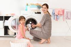 Huisvrouw met haar weinig dochter die wasserij thuis doen royalty-vrije stock fotografie