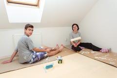 Huisvrouw met zoon het schilderen muur aan wit Royalty-vrije Stock Afbeeldingen