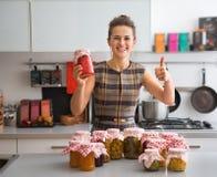 Huisvrouw onder kruiken met eigengemaakte vruchten jam Royalty-vrije Stock Foto