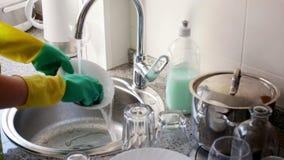 Huisvrouw in rubberhandschoenen die schotels wassen stock footage