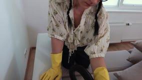 Huisvrouwen schoonmakende bank met dicht omhoog stofzuiger stock videobeelden