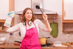 Huisvrouwenkok in keuken Stock Foto