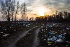 Huisvuil dichtbij de landweg met zonsondergangachtergrond Stock Afbeelding
